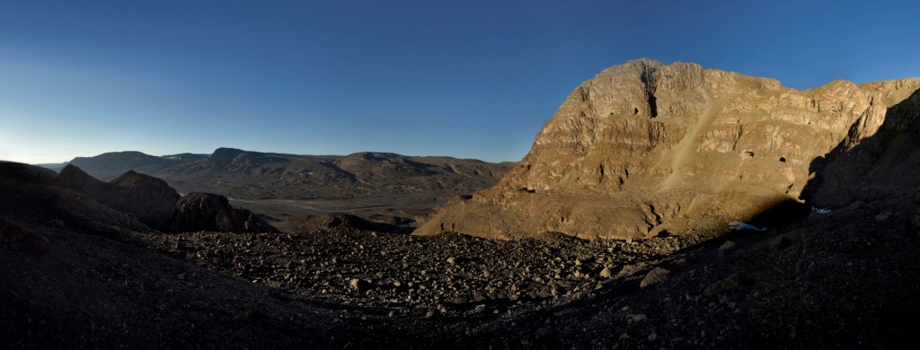 As the evening sunlight arrives, Mark Wright and Gina Moseley walk along a ridge bathed in sunlight towards Chris Blakeley stood upon a large lump of rock. In the distance and beyond Chris, Christoph Spötl stands in blue in the middle of the righthand entrance to The U-shaped cave. The giant scree slope, the largest of all the scree slopes of rocks the team endured on this expedition drops away in the middle of the cliff face, providing the access they needed to get into The Crystal Palace - Panorama of 9 portrait images 24mm