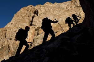 The team scramble up a steep scree slope to the highest level of caves